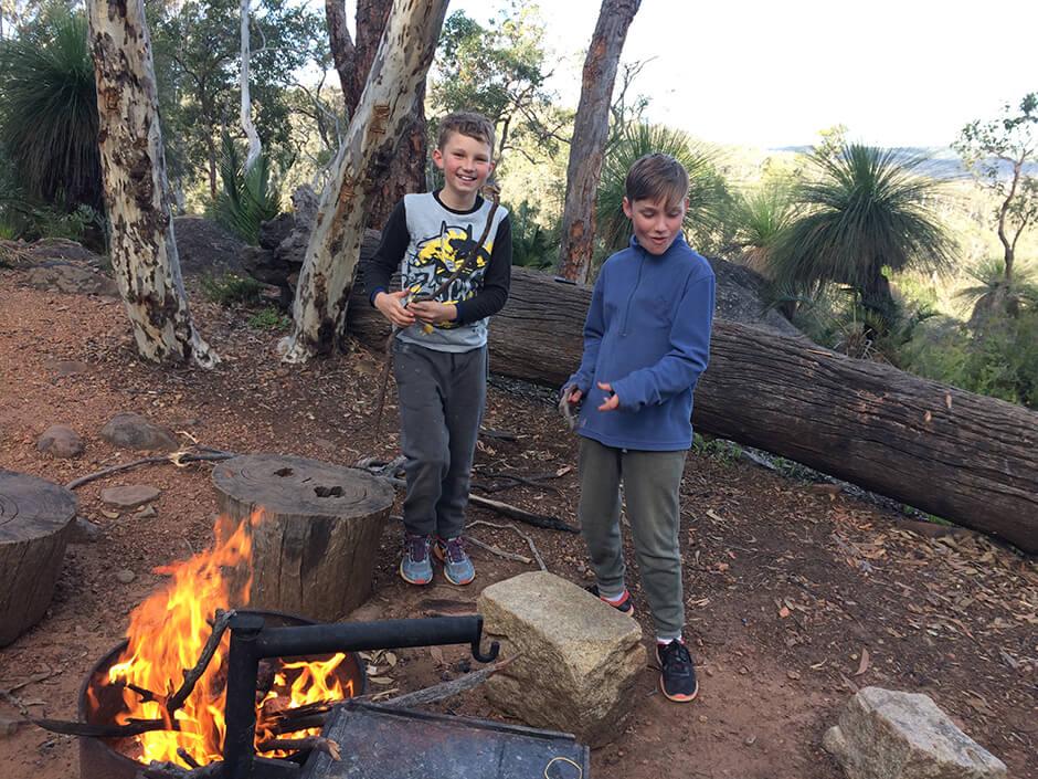 Teen treks boys at campfire Helena campsite