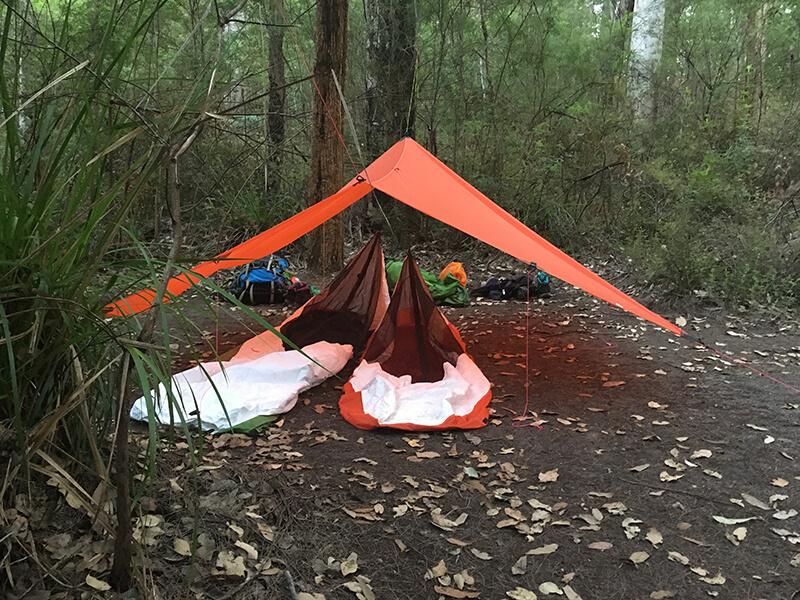Two ultralight sleeping cocoons under an ultralight tarp